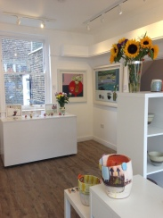 Paintings by Nancy Crewe (left) and Emma Dunbar (right) with ceramics by Linda Styles (front) and Remon Jephcott (back)
